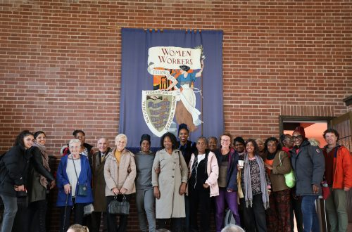 The group in front of a banner reading 'Women Workers'